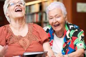 Senior-female-friends-laughing-while-using-digital-tablet